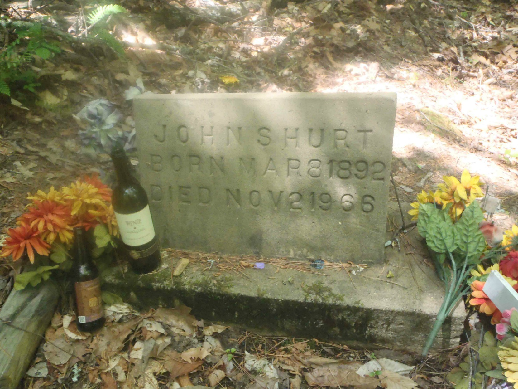 Tribute of flowers, liquor and other items left by fans on Mississippi John Hurt's grave