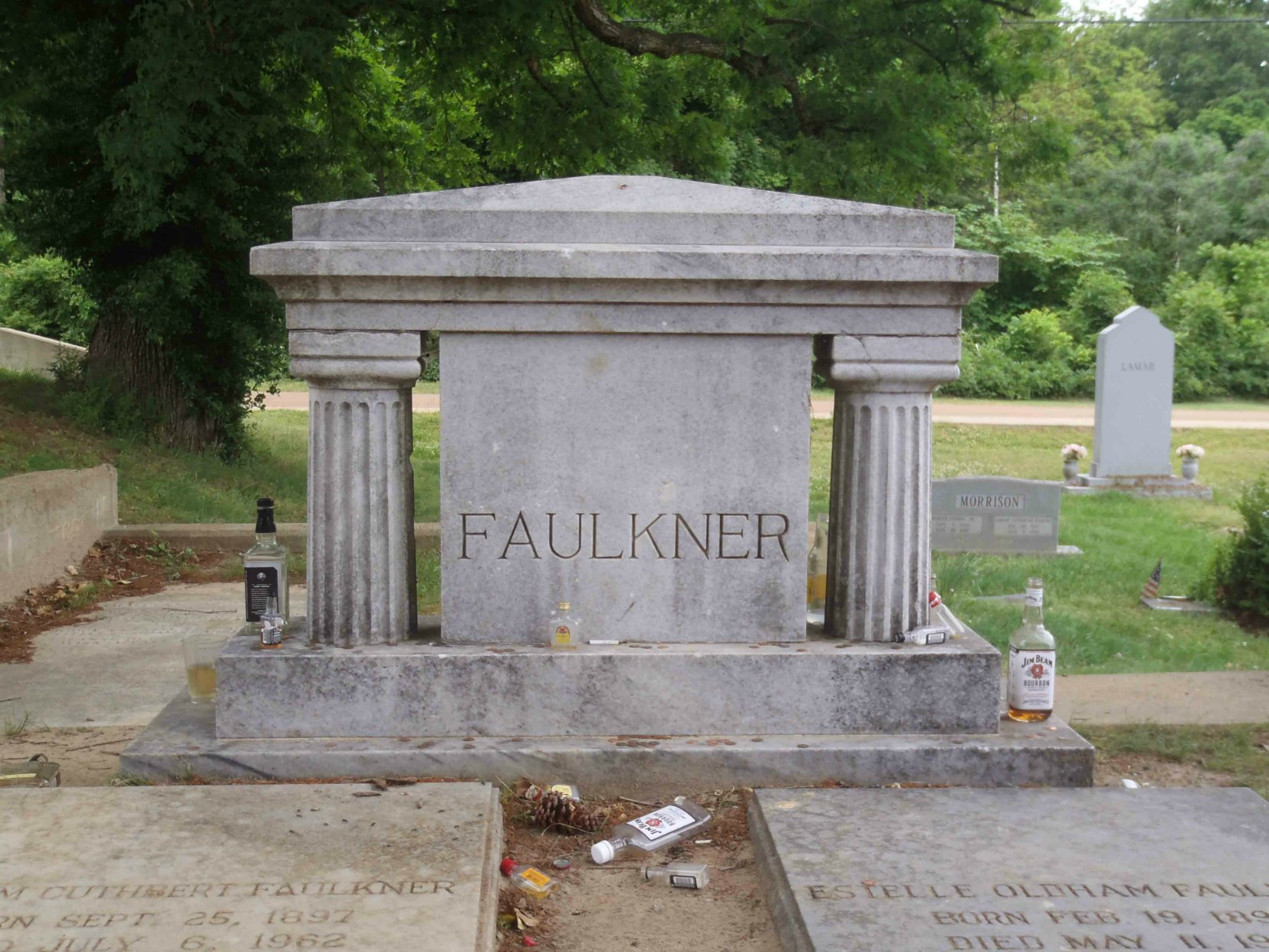 William Faulkner's grave in Oxford, Mississippi. The liquor bottles are tributes left at the grave by William Faulkner's fans.