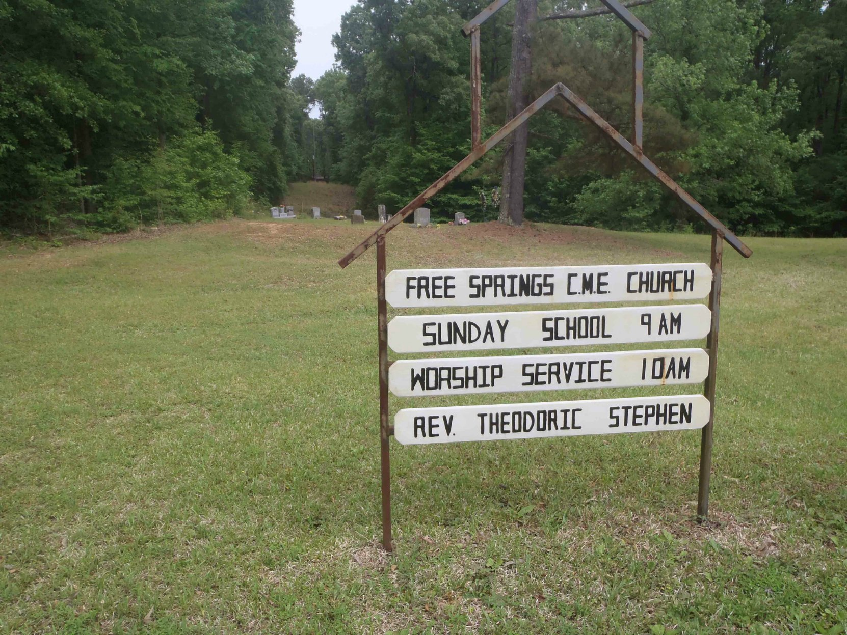 Free Springs C.M.E. Church sign as it appears from the road. R.L. Burnside's grave is in the cemetery visible behind the sign.